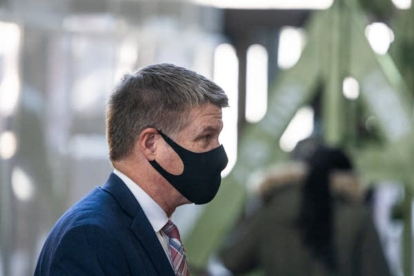A man with a black mask walks.