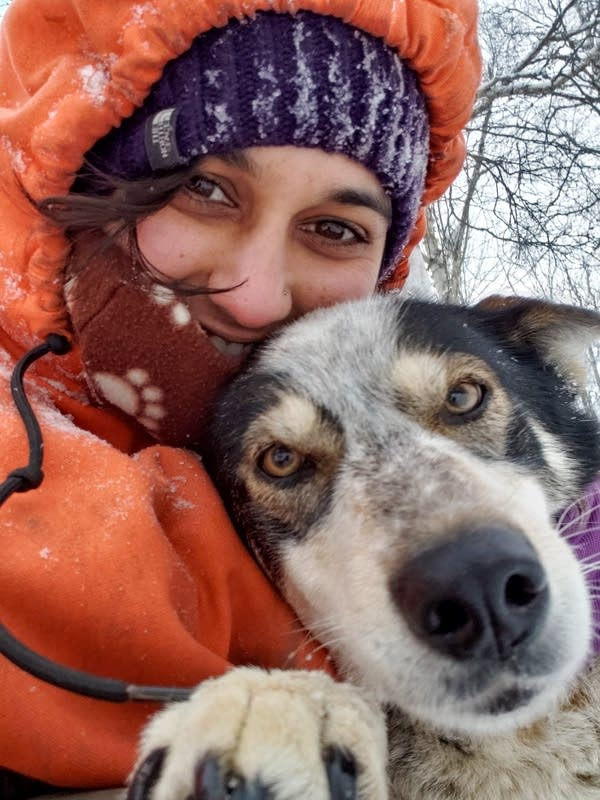 A woman poses for a photo with a sled dog