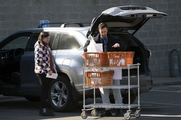 A person loads bags of groceries into a car.