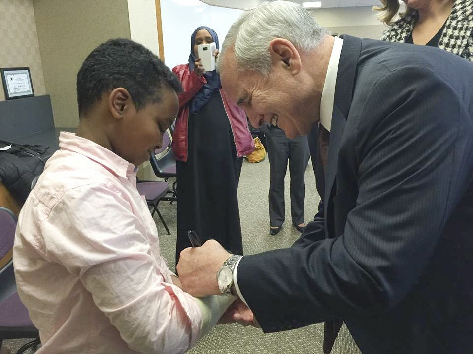Gov. Mark Dayton signs Yusuf Dayur's cast in 2015.