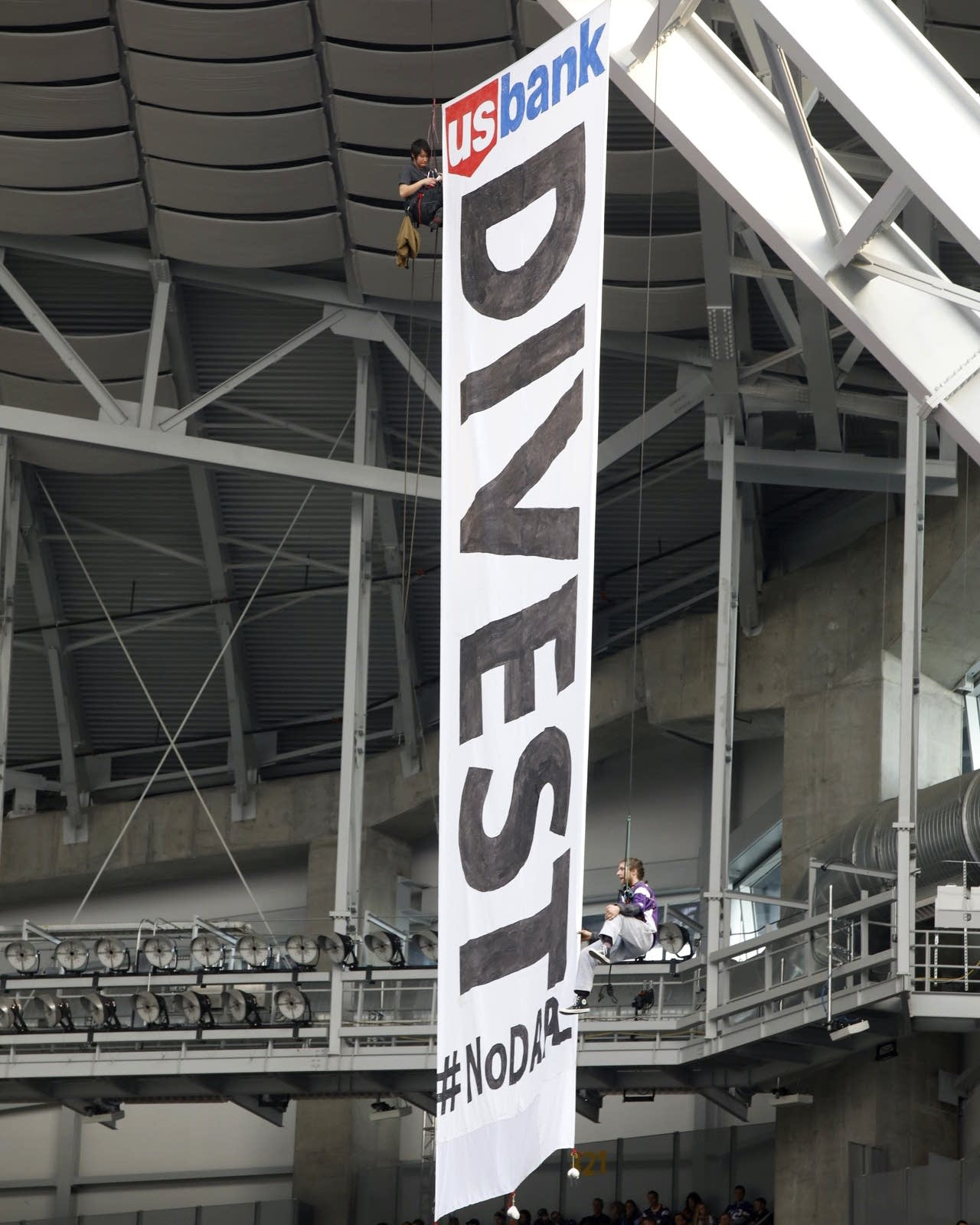 Protesters unfurl banner at Vikings game.