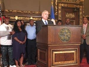 Gov. Mark Dayton speaks, surrounded by relatives of Philando Castile