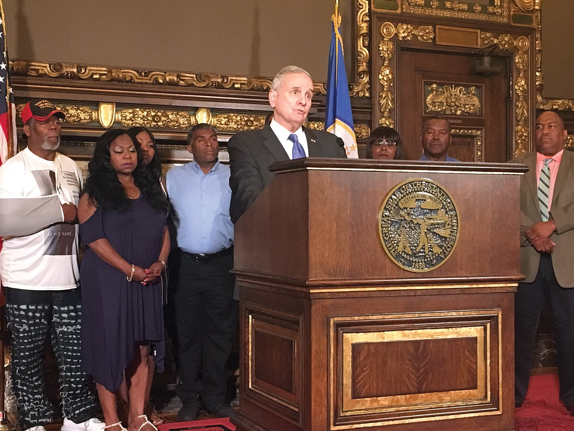 Gov. Mark Dayton speaks, surrounded by relatives of Philando Castile