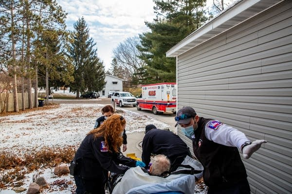 Four people push a person on a stretcher out to an ambulance.