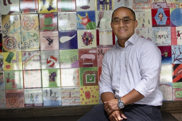 A man sit in front of wall with tiles featuring children's drawings.
