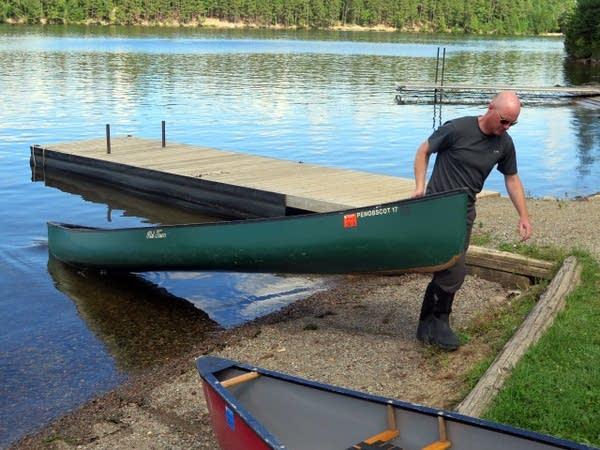 John O'Keefe pulls a canoe out of Moose Lake.