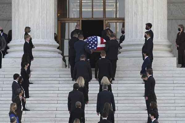 A flag-draped casket is carried into a building.