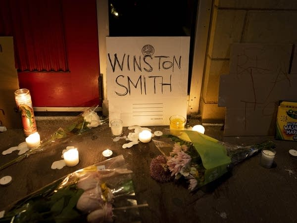 """A cardboard sign with """"Winston Smith"""" written on it, surrounded by candles."""
