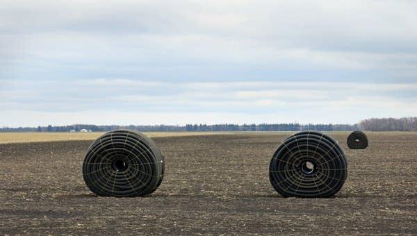 Large rolls of drain tile sat in a field.