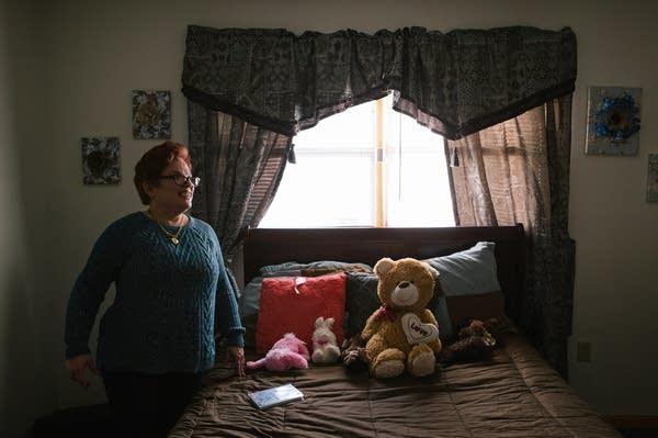Pauline stands in her room.