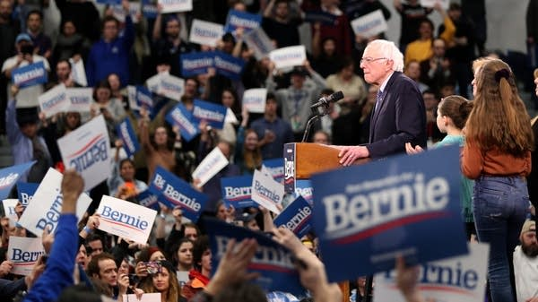 Bernie Sanders stands on a stage surrounded by supporters.
