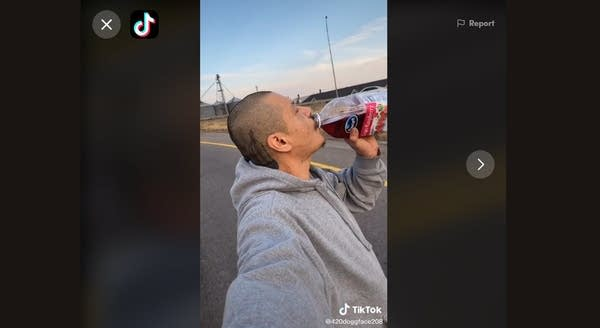 Still from TikTok of man drinking cranberry juice from bottle on longboard