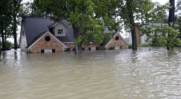 A home is surrounded by floodwaters from Tropical Storm Harvey.