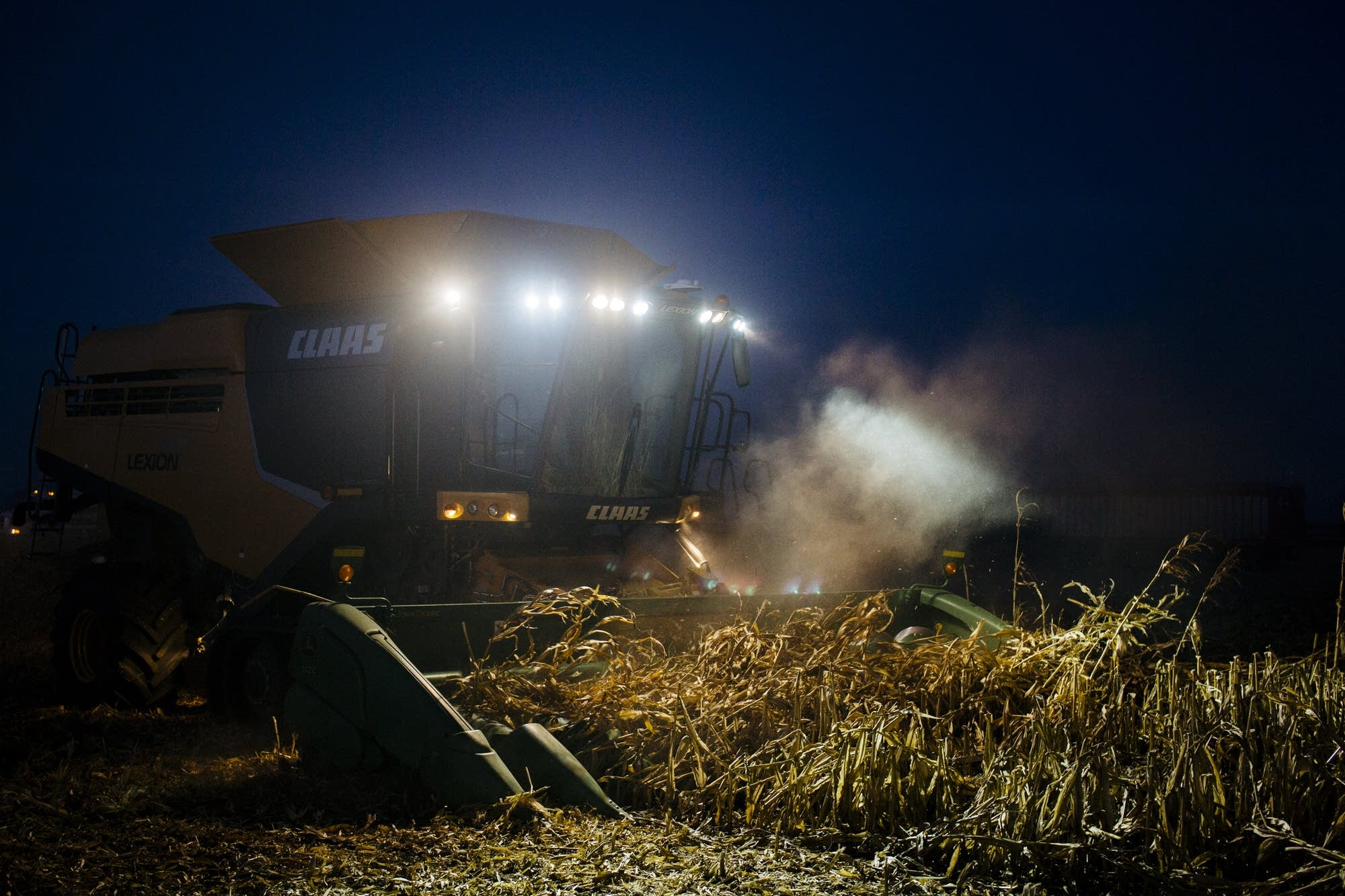 The combine lights up corn debris.
