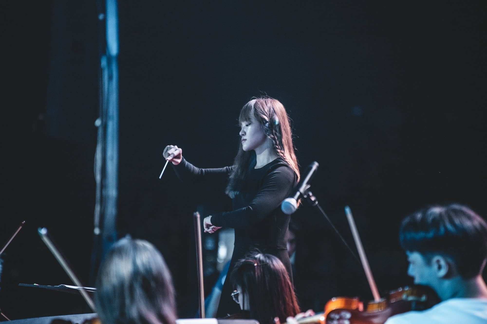 The conductor gives the orchestra the tempo.