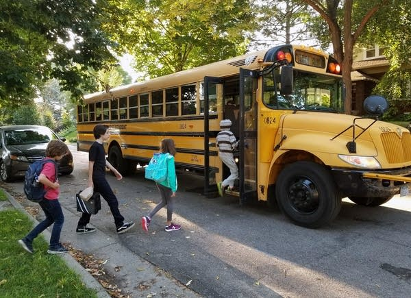 Students get on a school bus in St. Paul.
