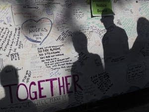 Shadows of people looking at messages of condolences.