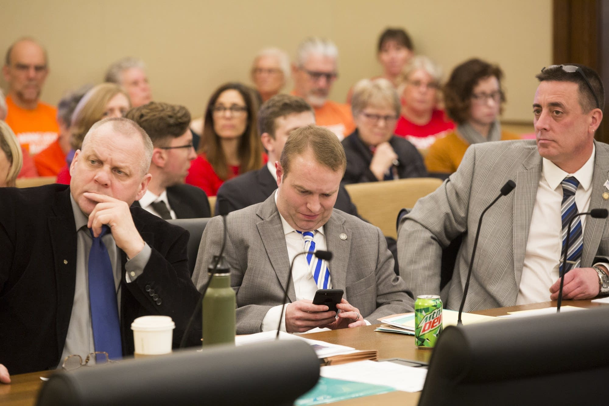 GOP Rep. Nick Zerwas looks at his phone