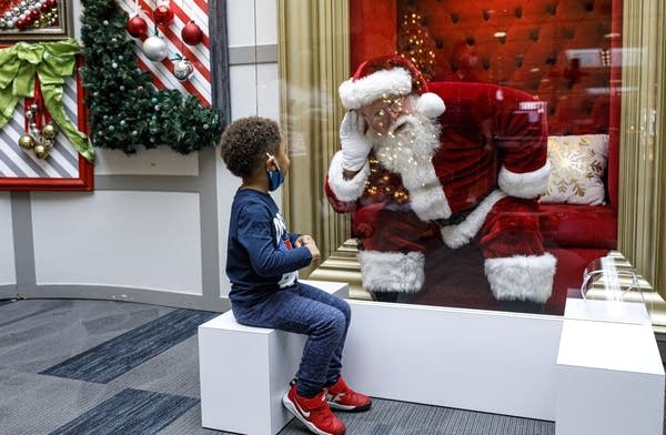 A kid visits with Santa Claus, with safety protocols in place