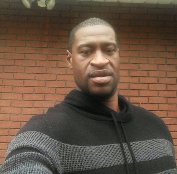 A man wearing a black and gray sweater.