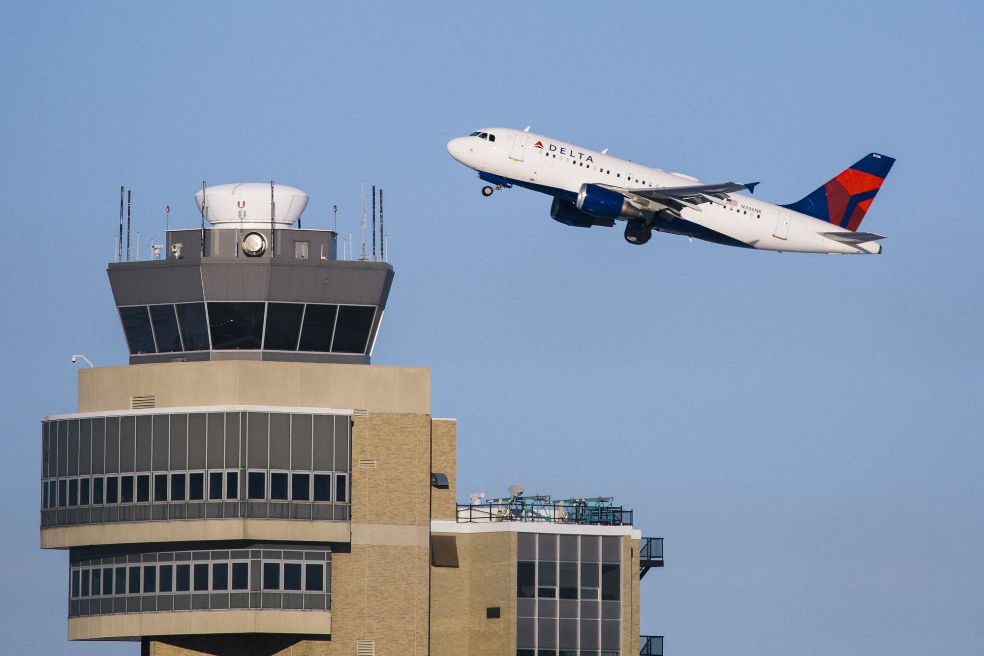 A Delta jet cruises past the air traffic control tower.