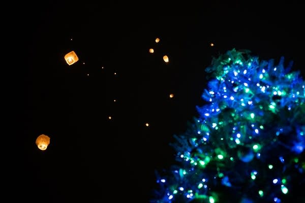 Peace lanterns float above a Christmas tree lit for Jayme Closs.