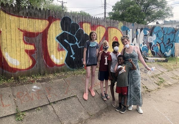 A transracial family poses in front of a wooden fence with graffiti art.