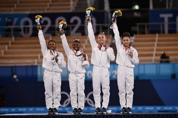 Four gymnasts hold their silver medals.