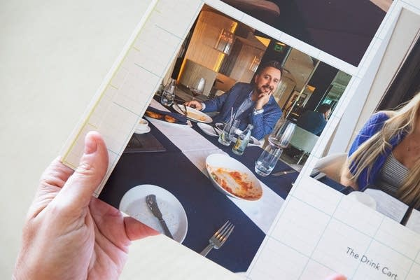 A hand holds a book with a photo of a man at a dining table.