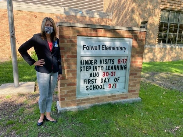 a woman stands next to an elementary school