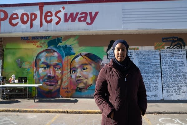 A woman stands in front of a gas station with painted doors.
