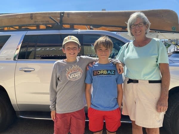 A woman and two young boys pose for a photo in front of a car.