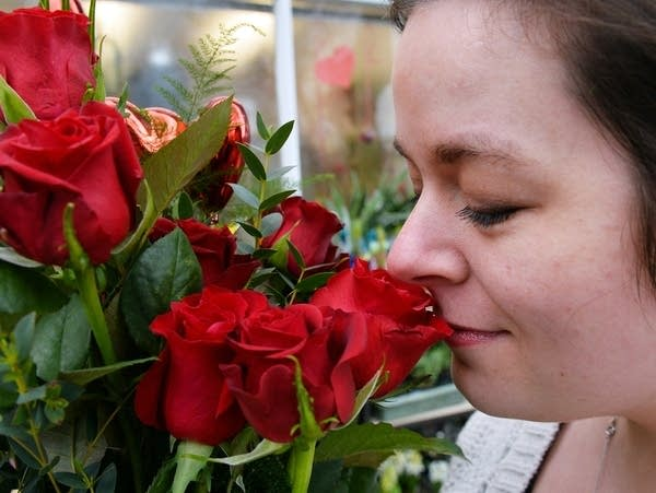 A woman smells a bouquet of roses