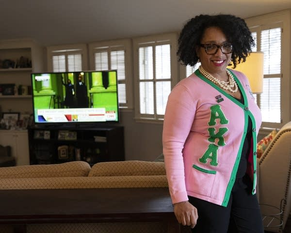 A woman wearing a pink and green sweater and pearls.