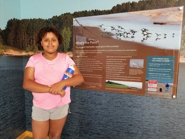 A young girl stands for a photo next to a sign with nature information.