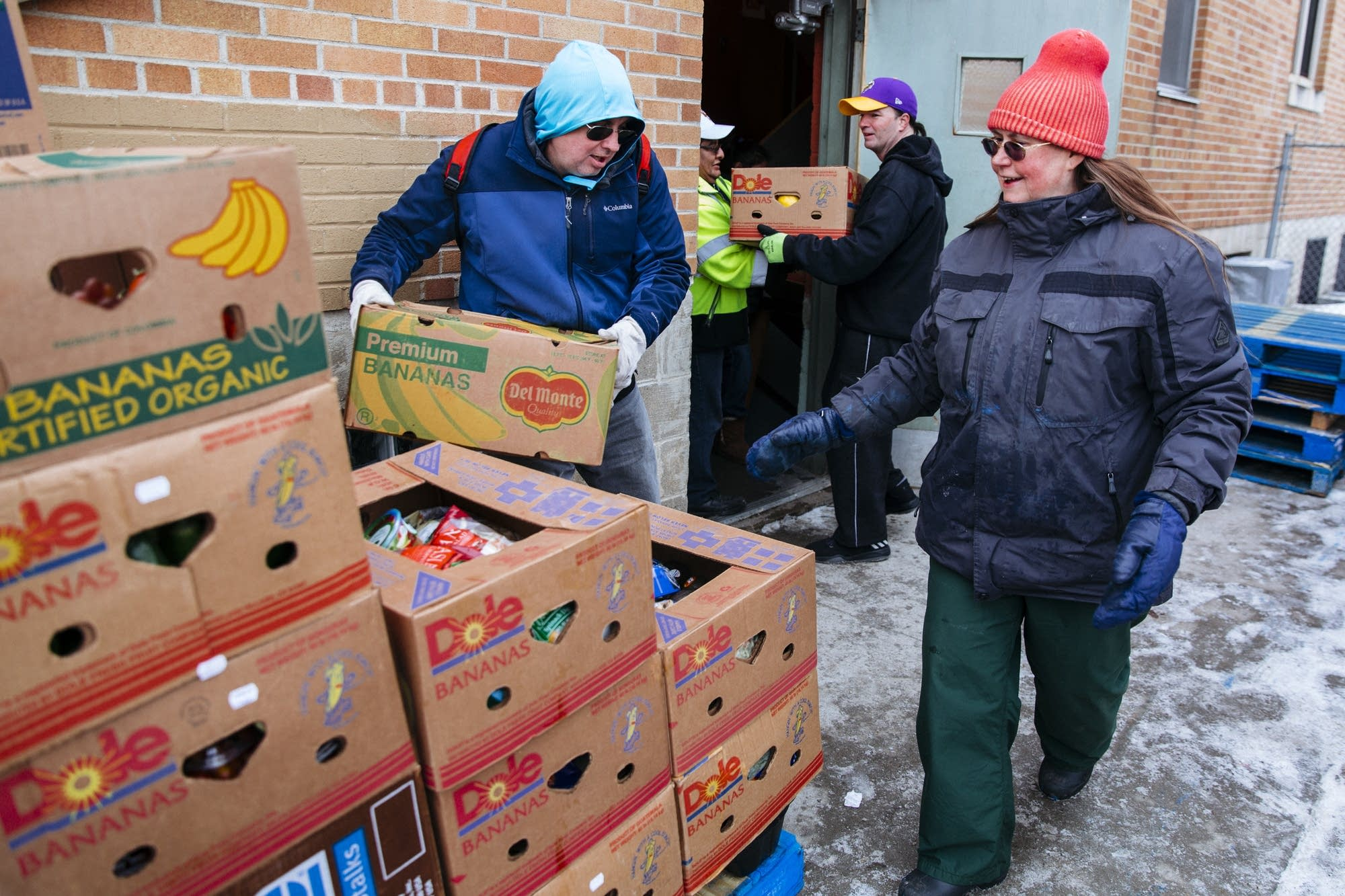 Volunteers pass food into the basement of Jericho Road.