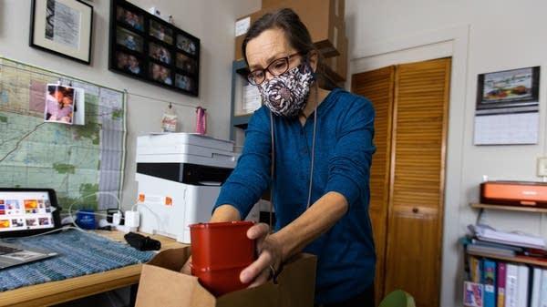 A woman puts supplies into a paper bag.