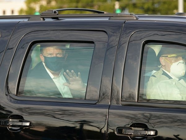 President Donald Trump waves from the back of an SUV