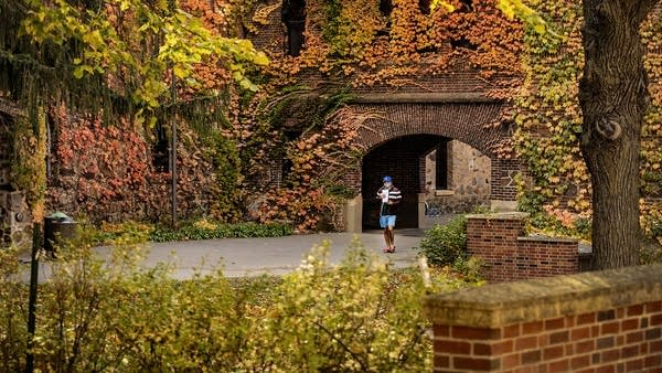 A person wearing a face mask walks through campus.