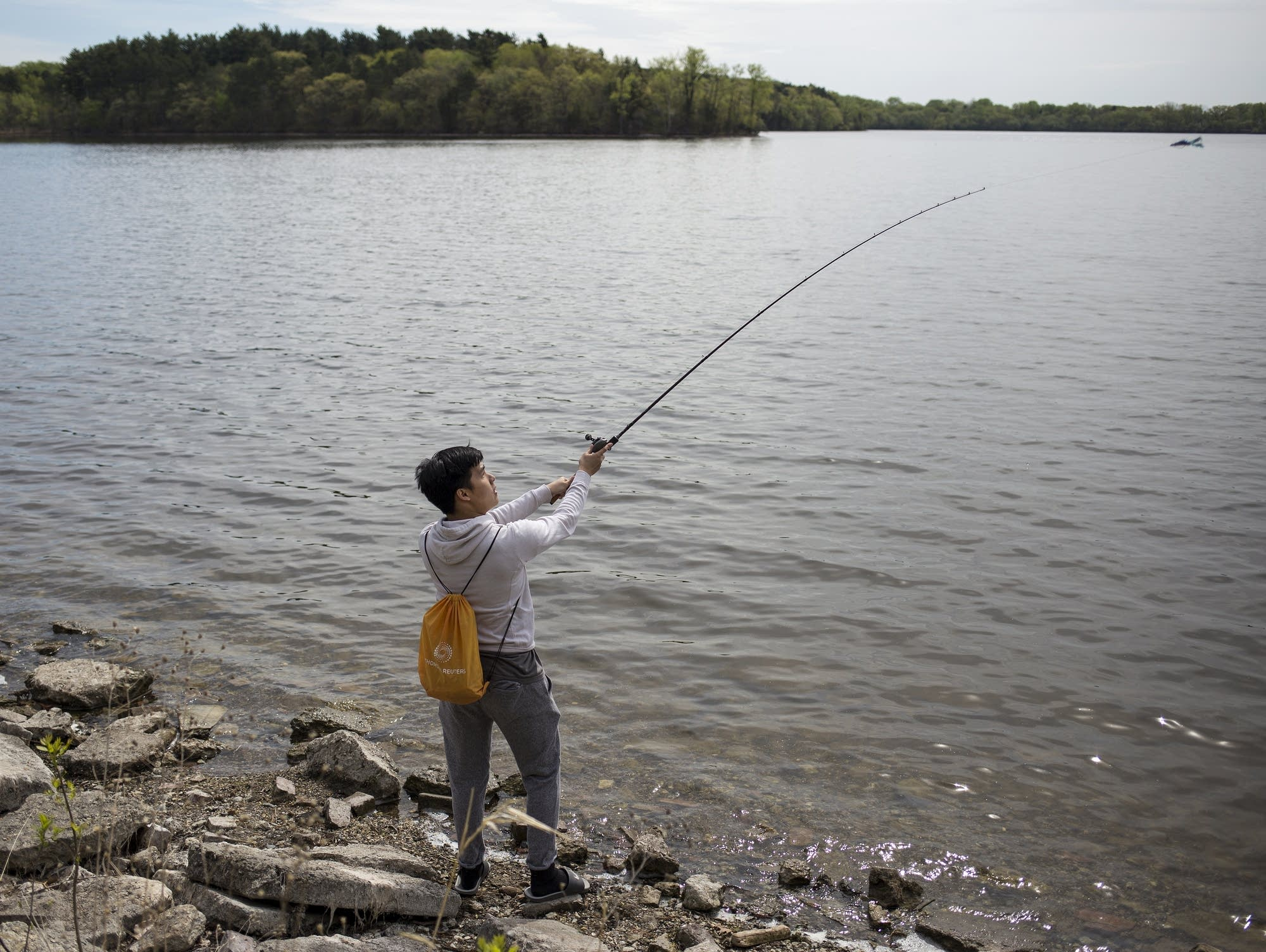 Nikls Chang of St Paul casts his line at Vadnais Lake