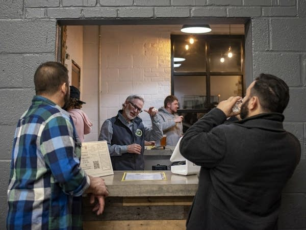 Co-founder Mark Burke signs with patrons at Streetcar 82 Brewing