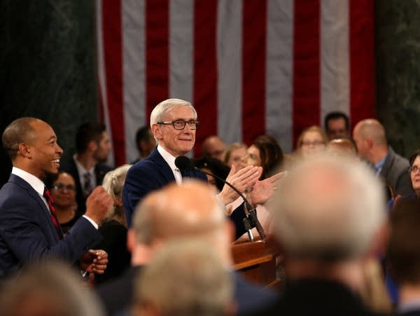 Gov. Tony Evers of Wisconsin surrounded by lawmakers and professionals.
