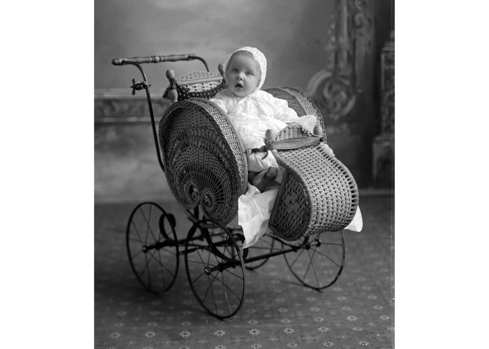 A baby in an elaborate wicker stroller.