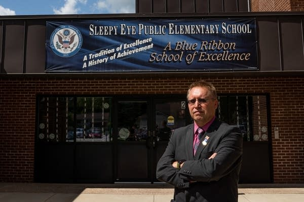 A man stands in front of a brick school building.