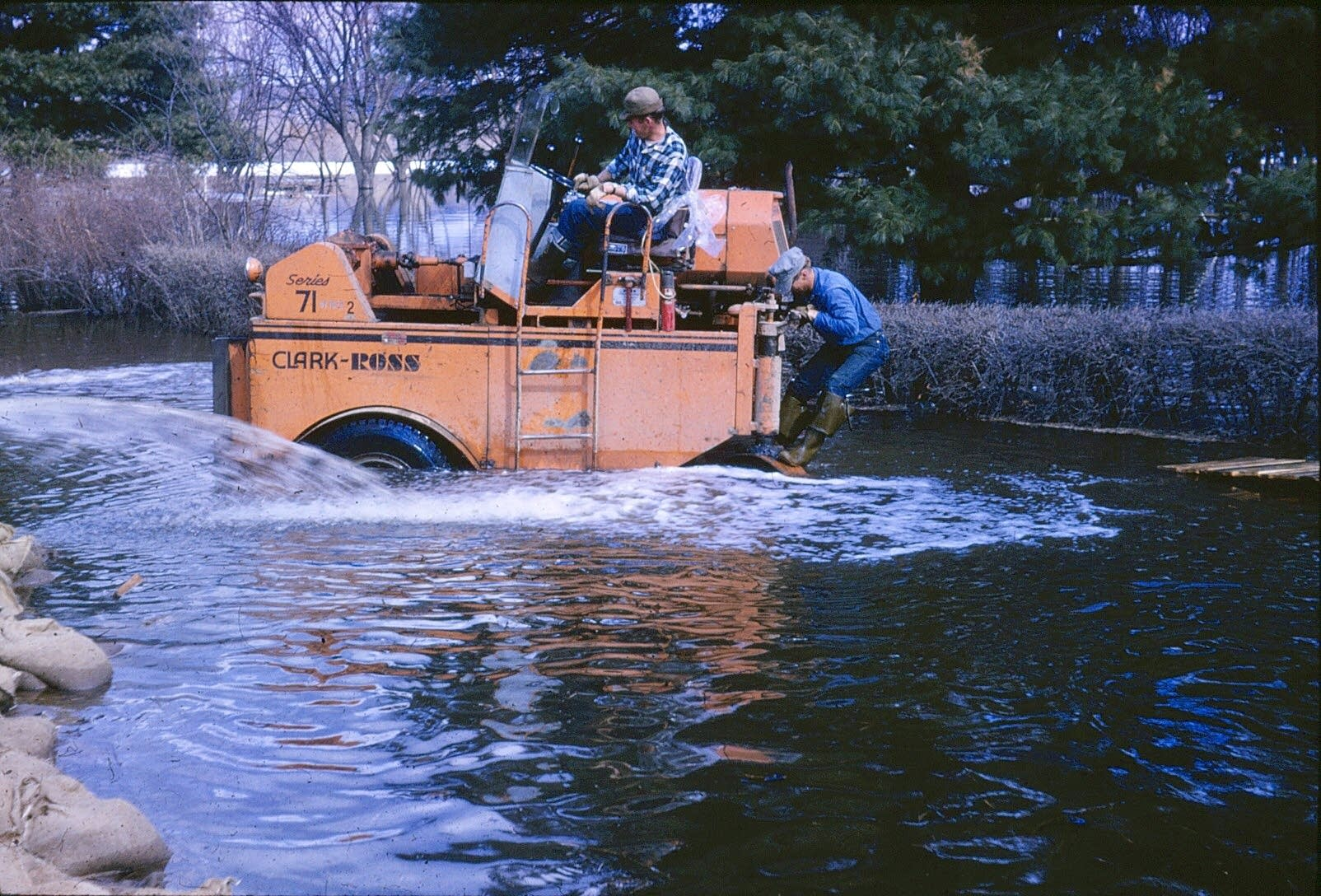 Two men ride a tractor through floodwaters.