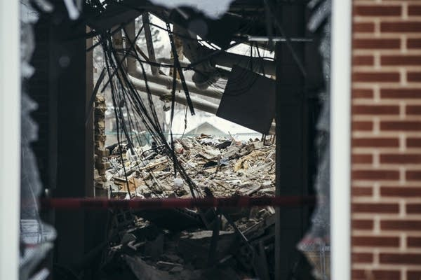 Rubble is seen through a blown out window.