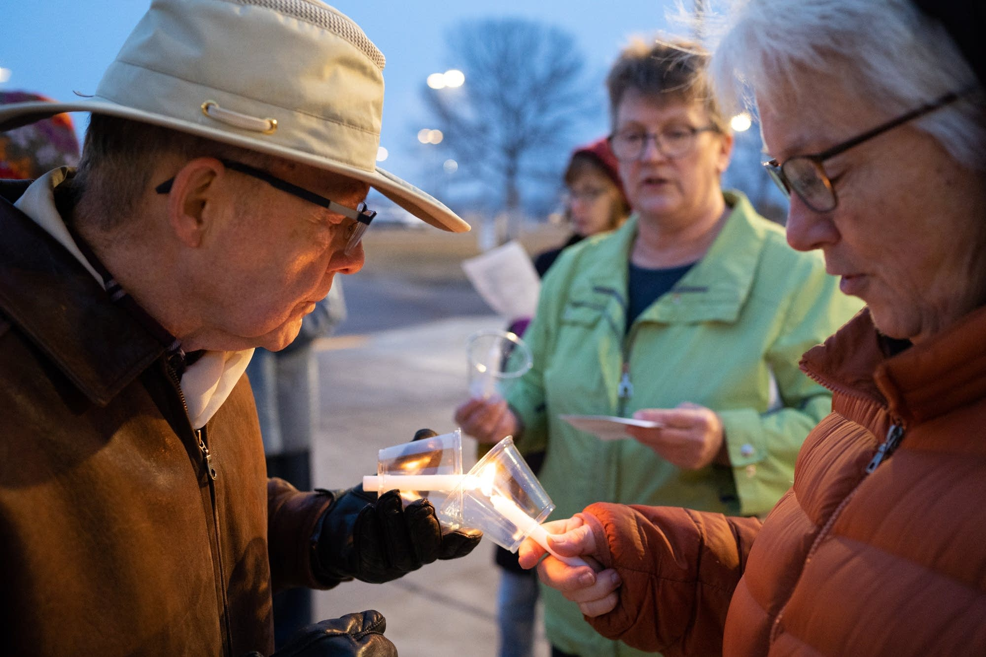 Lawrence Cook, left, lights his candle with Gigi Nauer's.