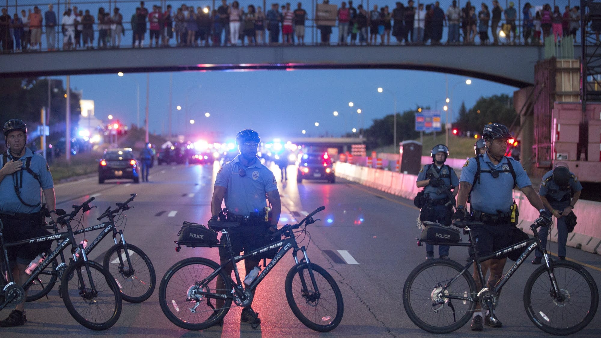 Bike police hold a line while protesters watch.