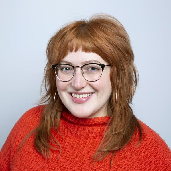 A woman wearing glasses and an orange sweater smiles.