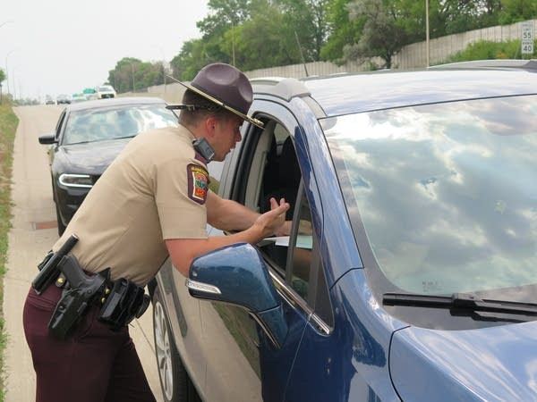 A state trooper pulls over a driver.